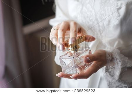 Close Up Photo Of A Luxury Perfume Flacon Being Opened In Manicured Hands Of Elegant Bride Wearing W