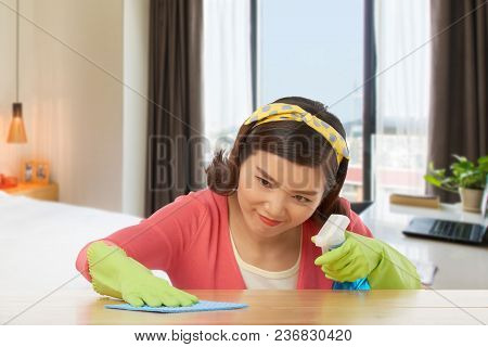 Woman With Obsessing Compulsive Disorder Wiping Stain Off From The Table Surface