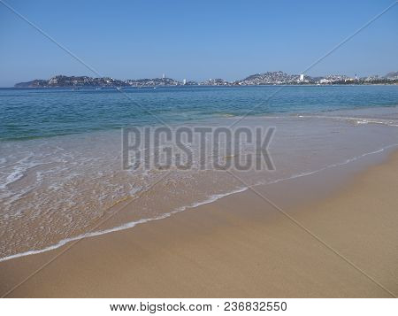 Panorama Of Seaside View Of Sandy Beach At Bay Of Acapulco City In Mexico And Waves Of Pacific Ocean