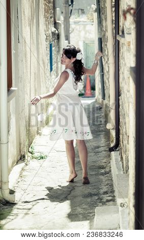 A Young Girl In White Dress Walking Through The Narrow Street