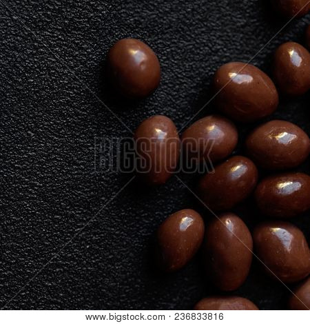 Chocolate Candy Background. Dark Brown Chocolate Round Candies On Black Concrete Background  Top Vie