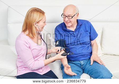 Young woman makes blood pressure measurement at a senior in home nursing