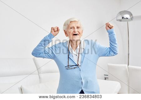 Senior celebrates with clenched fists in her apartment or in the senior residence