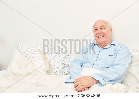 Smiling senior as a bedridden patient lies in the double bed at home