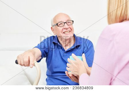 Smiling senior with a mug of coffee being cared for in home care