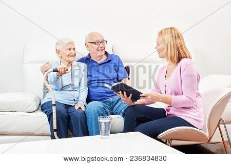 Young volunteer woman reads stories from a book to seniors