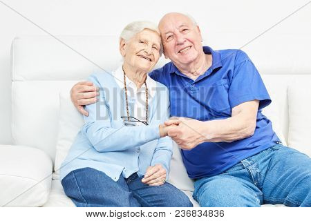 Happy loving senior couple is holding hands on the couch at home