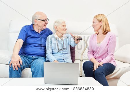 Senior couple with laptop computer and a young woman in retirement home