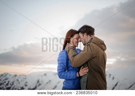 Beautiful Couple-a Girl And A Guy-in Warm Winter Things Gently Embrace Each Other On The Background