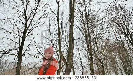 A young schoolgirl joyfully throws a snowball and breaks it with a palm when it falls. Emotions of joy. Winter fun in nature in the forest poster
