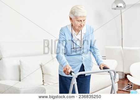 Senior as a patient with handicap learns to walk with the walking frame in the rehab