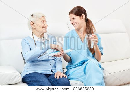 Smiling senior woman receives a drug from nursing wife in retirement home