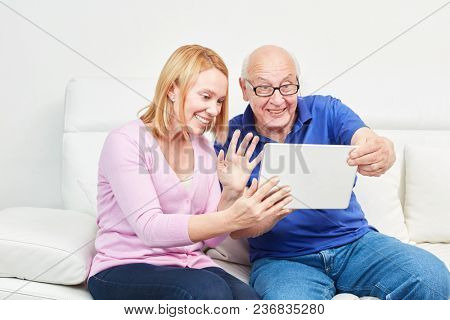 Young woman and a senior with laptop PC have fun at a video chat at home