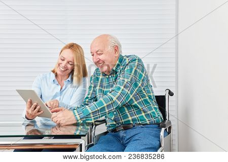 Young woman as daughter with senior as father have fun with a tablet PC