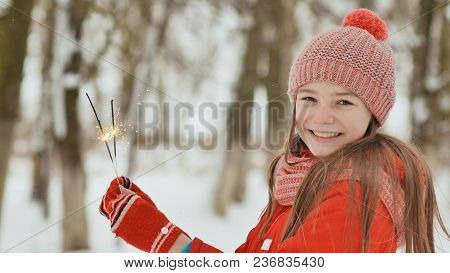 The Charming Young Schoolgirl Joyfully Holds In Her Hands A Packaged Box With A Gift In The Winter F