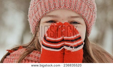 Portrait Of A Young Schoolgirl With Freckles In The Woods In Winter. He Warms His Hands In Mittens A