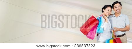 Couple with shopping bags against cream motion blur