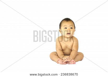 Asian Baby Boy Sitting And Smile In Front Of An Isolate White Background. He Put His Hand On Leg. He