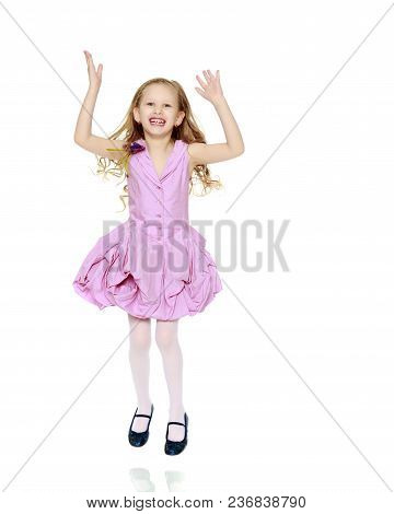 Happy Little Blond Girl, With Long Curly Hair, In A Beautiful Pink Dress Above The Knees.she Jumps J