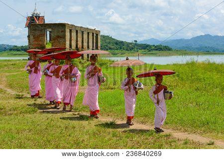 Kanchanaburi, Thailand - July 24, 2016: Group Of Mon Nuns In Pink Robes Holding Umbrella Walking Out