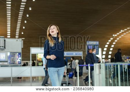 Pretty Female Person Walking At Airport Hall With Neck Pillow On Valise. Concept Of Movith To Anothe