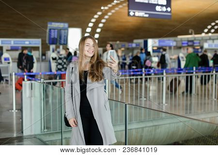 Female Person Making Selfie By Smartphone Front Camera At Airport. Concept Of Social Networks And Tr