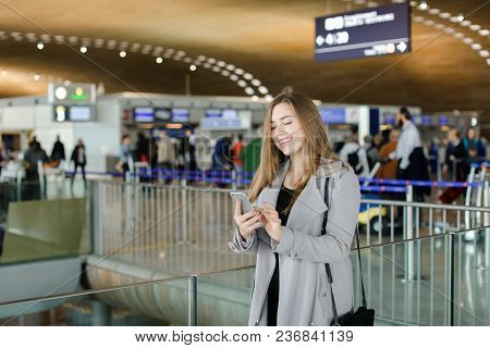 Nice Woman Typing Message By Smartphone At Airport, Wearing Coat. Concept Of Chatting And Free Hotsp
