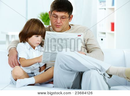 Photo of cute boy and his father reading newspaper together at home