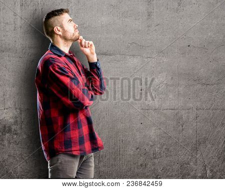 Young handsome man thinking and looking up expressing doubt and wonder