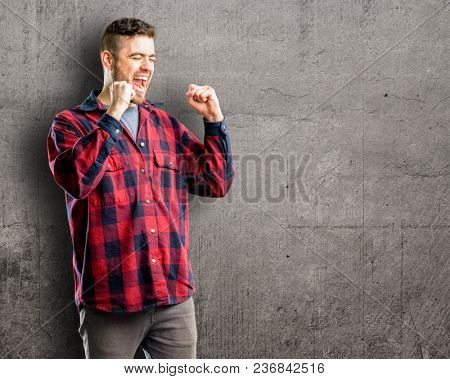 Young handsome man happy and excited expressing winning gesture. Successful and celebrating victory, triumphant