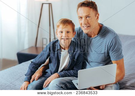 Family Values. Positive Nice Delighted Father And Son Sitting Together And Looking At You While Usin