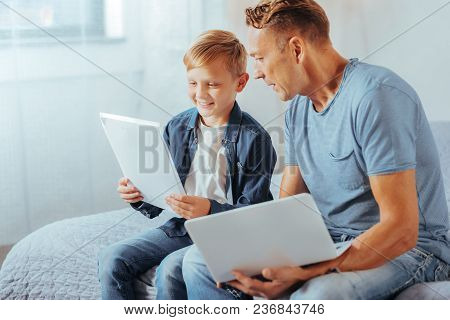 Good Job. Positive Nice Pleasant Man Holding A Netbook And Looking At His Sons Drawings While Suppor