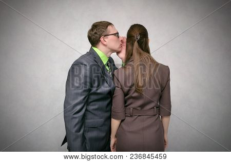 Curious And Amazed Young Woman Listens Attentively A Businessman Isolated On Gray Background. Tellin