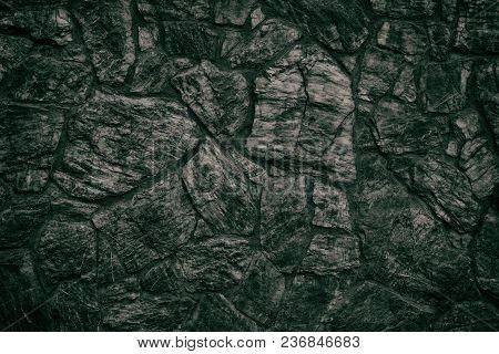 Emerald Black Stone Wall Texture. Dark Green Rough Rock Masonry Surface. Gloomy Sinister Background
