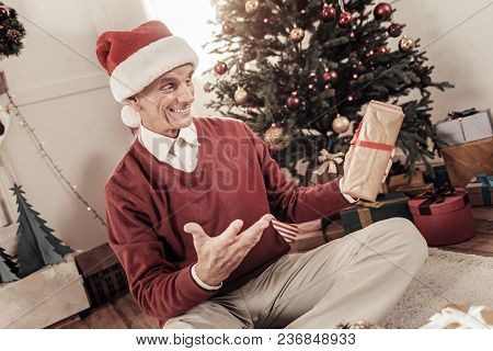 So Pleased. Positive Male Wearing Special Hat And Keeping Smile On His Head While Holding Gift Box