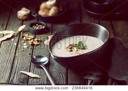 Mushroom Cream Soup In A Bowl Over Dark Wooden Background
