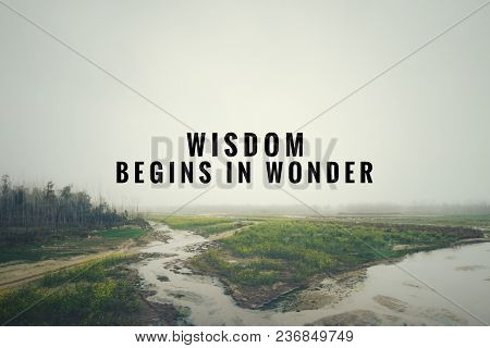 Motivational And Inspirational Quote - Wisdom Begins In Wonder. With Blurred Vintage-styled Backgrou