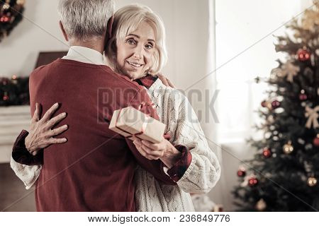 Warm Hugs. Attractive Elderly Female Smiling While Holding Present And Looking At Camera