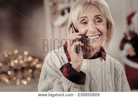 Waiting For You. Elderly Female Person Expressing Positivity And Holding Telephone Near Right Ear Wh