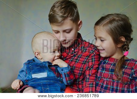 Three Children At Home Wearing Clothing With The Same Ornament