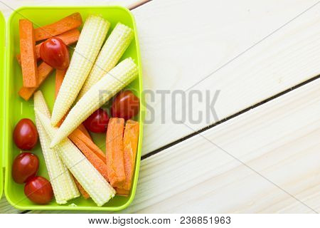 Healthy Lunch Concept. Baby Corns, Cherry Tomatoes, Carroots In A Green Lunch Box, Light Wooden Back