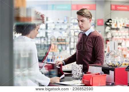 Portrait of a handsome young man smiling while buying an useful pharmaceutical product in a modern drugstore with various medicines and helpful personnel