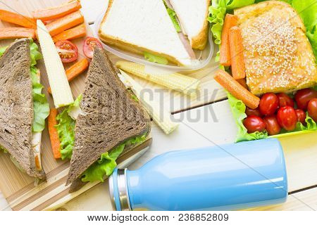 Healthy Lunch Concept. Lunch Box Food Assortment: Rye And Wheat Bread Sandwich, Vegetables Blue Bott