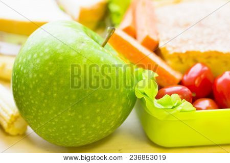 Healthy Lunch Concept. Green Apple And Lunch Box With Sandwich And Vegetables, Close Up