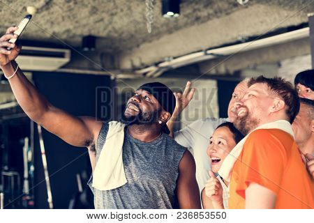 Group of diverse friends taking selfie together at the gym