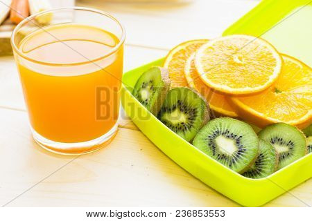 Healthy Lunch Concept. A Green Lunch Box With Sliced Orange And Kiwi, A Glass Of Juice, Light Wooden