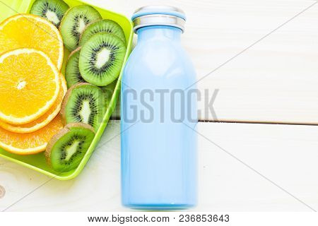 Healthy Lunch Concept. A Green Lunch Box With Sliced Orange And Kiwi, Blue Bottle, Light Wooden Back