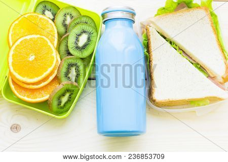 Healthy Lunch Concept. A Green Lunch Box With Sliced Orange And Kiwi, Blue Bottle, Sandwich In A Box