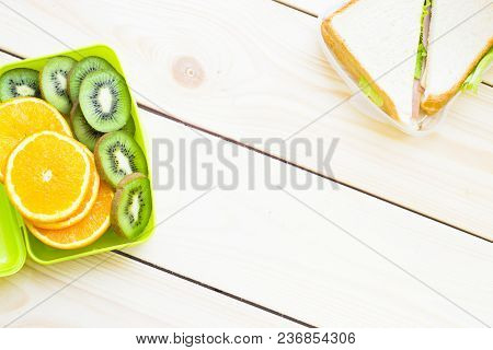Healthy Lunch Concept. A Green Lunch Box With Sliced Orange And Kiwi, Sandwich In A Box, Light Woode