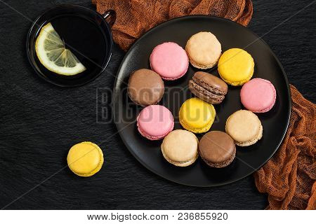 Different Macaroon On Black Plate And Tea With Lemon In Black Cup On Slate Background. Delicious And